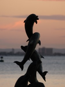 Dolphin statue at sunset